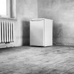 Der leere Kühlschrank im leeren Zimmer.