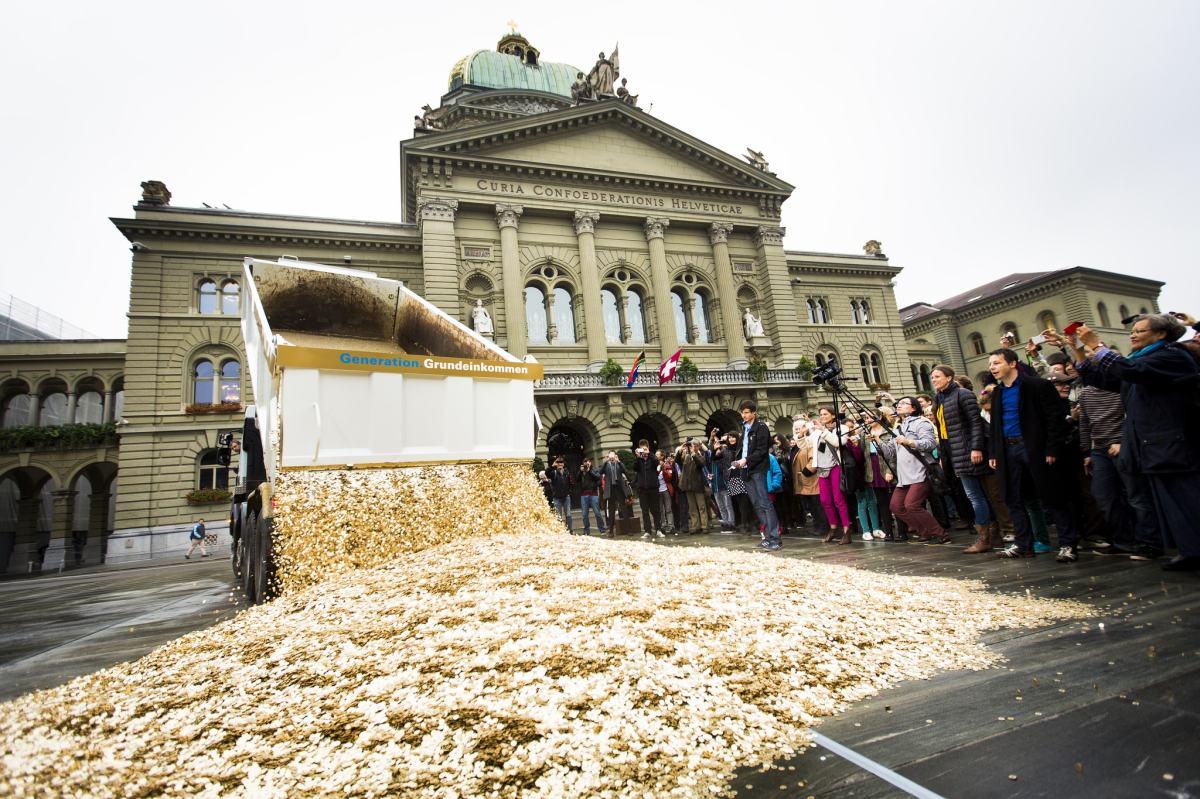 """Die Generation Grundeinkommen schüttete am 4. Oktober 2013 um 10.15 Uhr 8 Millionen """"Fünferli"""" auf den Bundesplatz."""