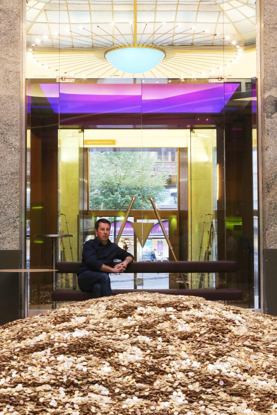Geld für alle? Daniel Häni vor einem Berg aus Münzen im Kaffeehaus unternehmen mitte in Basel.