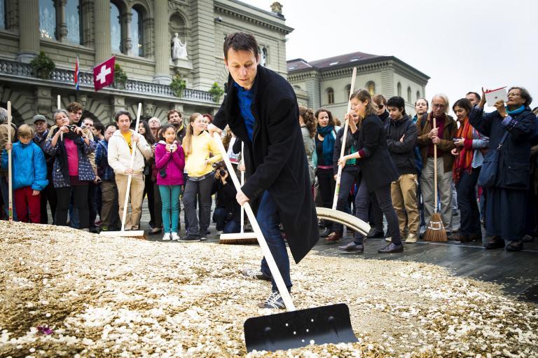 """Die Volksinitiative """"Für ein bedingungsloses Grundeinkommen"""" kippte symbolisch vor dem Schweizer Parlament acht Millionen Münzen aus."""