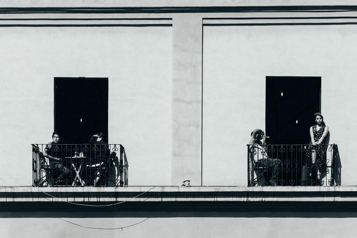 Menschen sitzen und stehen auf Balkons in der Sonne.