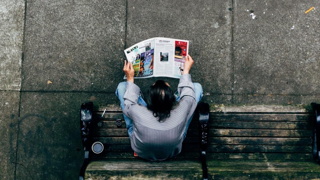 Mann auf der Bank mit einem Magazin. (Foto: Mike-Ackerman, Unsplash.com)