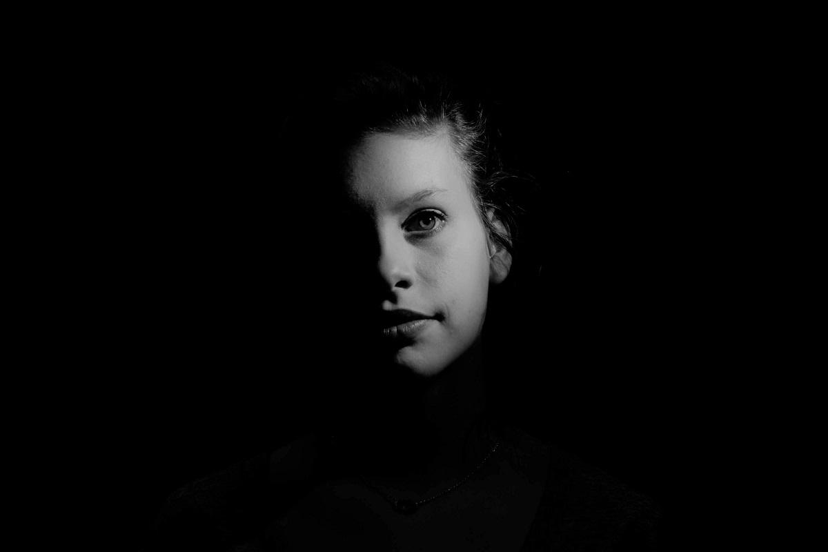 Ein Gesicht im Dunkeln nur teilweise erkennbar. (Foto: atc-commphoto, Unsplash)