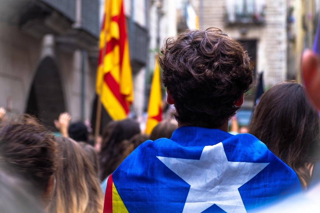 Mann mit umgehängter Fahne von Katalonien. (Foto: Marc Sendra Martorell, Unsplash.com)