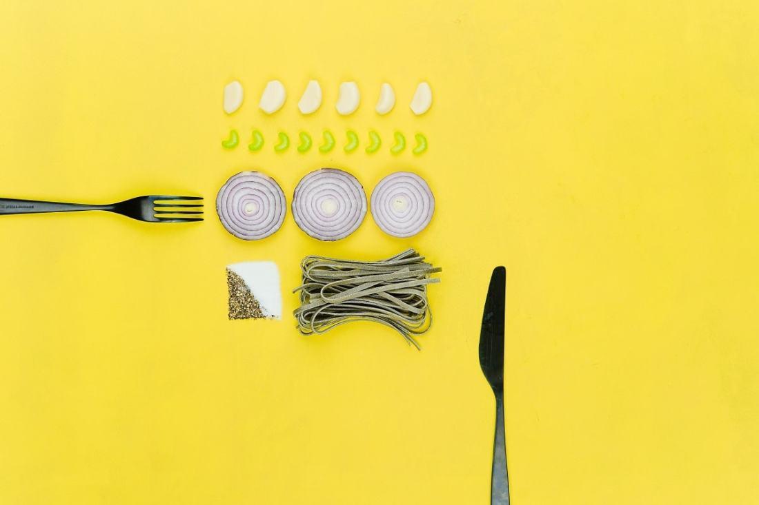 Messer, Gabel und Gemüse auf gelbem Grund. (Foto: Toa Heftiba, Unsplash.com)