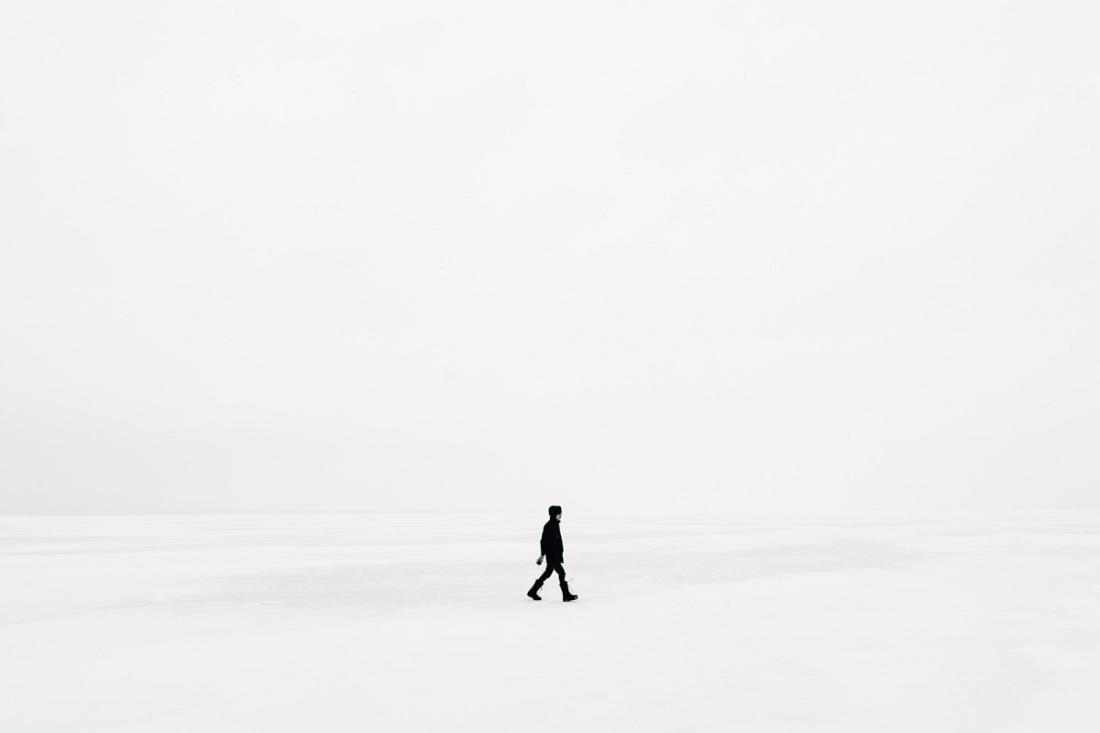 Ein Mensch geht über ein Schneefeld. (Foto: Emile Seguin, Unsplash.com)