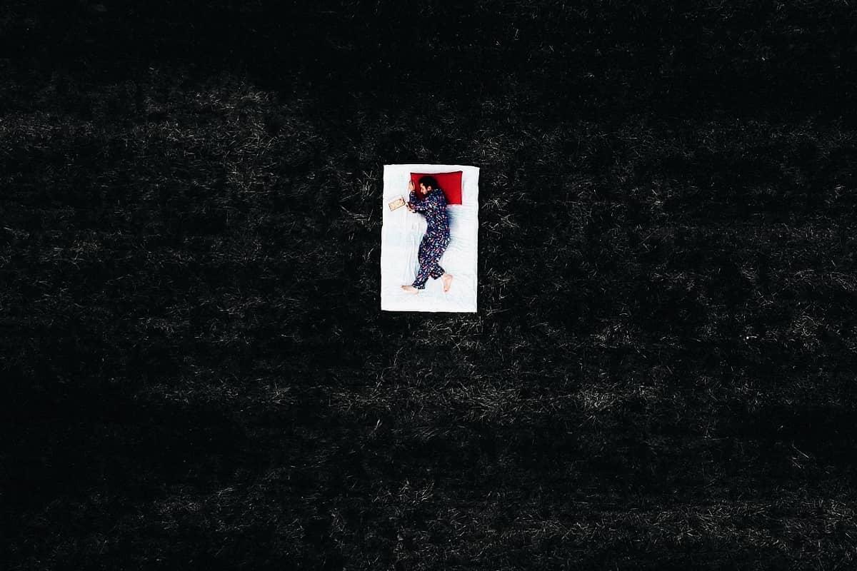 Ein ruhender Mensch auf einem weißen Bett. (Foto: Ahmet Ali Agir, Unsplash.com)