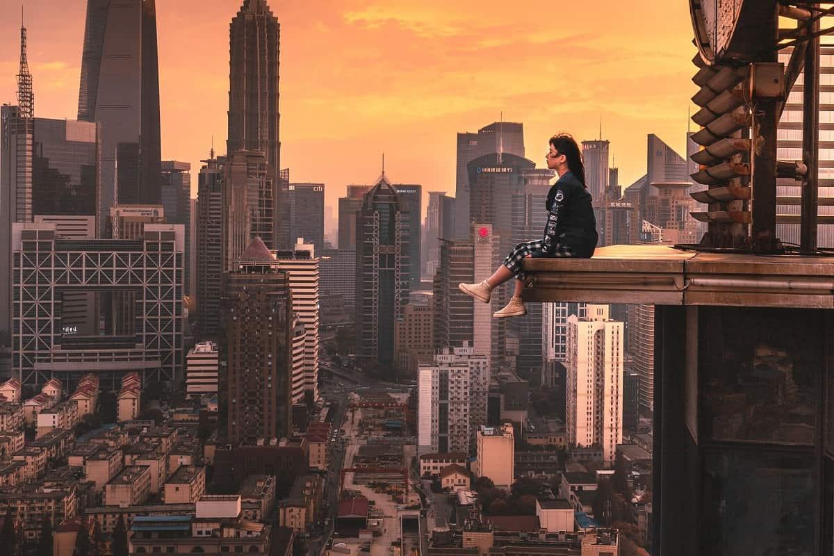 Eine Frau sitzt auf dem Vorsprung eines Hochhauses. (Foto: Yiran Ding, Unsplash.com)