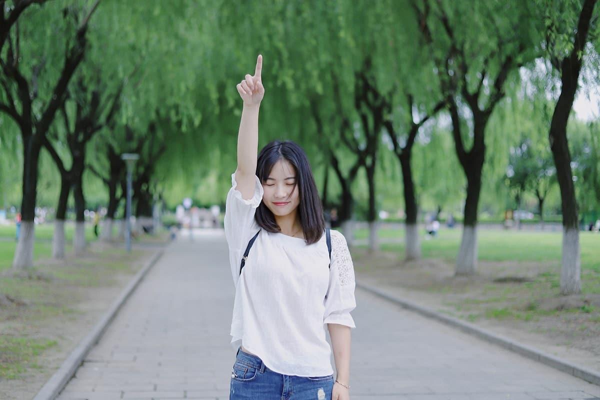 Frau zeigt zum Himmel. (Foto: Wang Xi, Unsplash.com)
